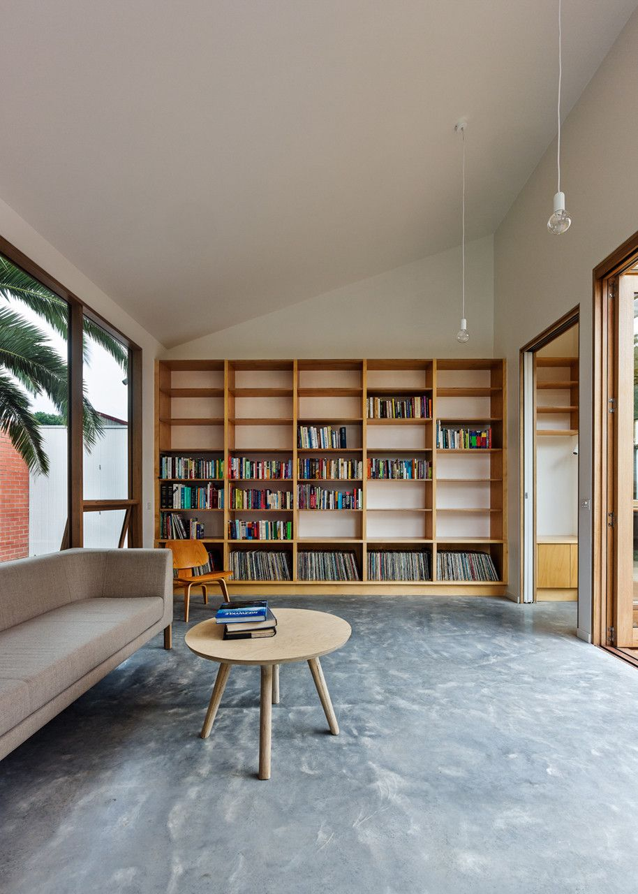 a modern home library with a large shelving unit, comfy contemporary furniture and a glazed wall