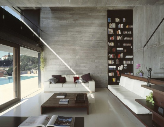 a modern to minimal home library with built-in bookshelves, stylish white seatign furniture and a glazed wall for natural light