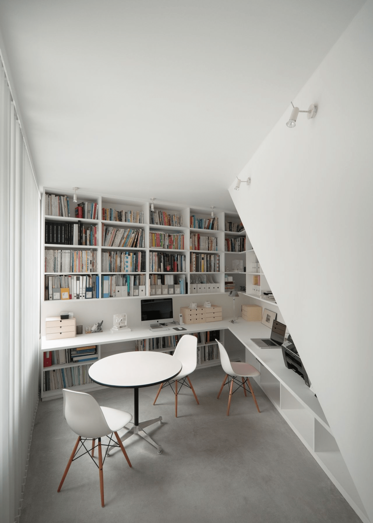 a modern home office and library in one, with built in bookshelves plus a built in floating desk and chairs