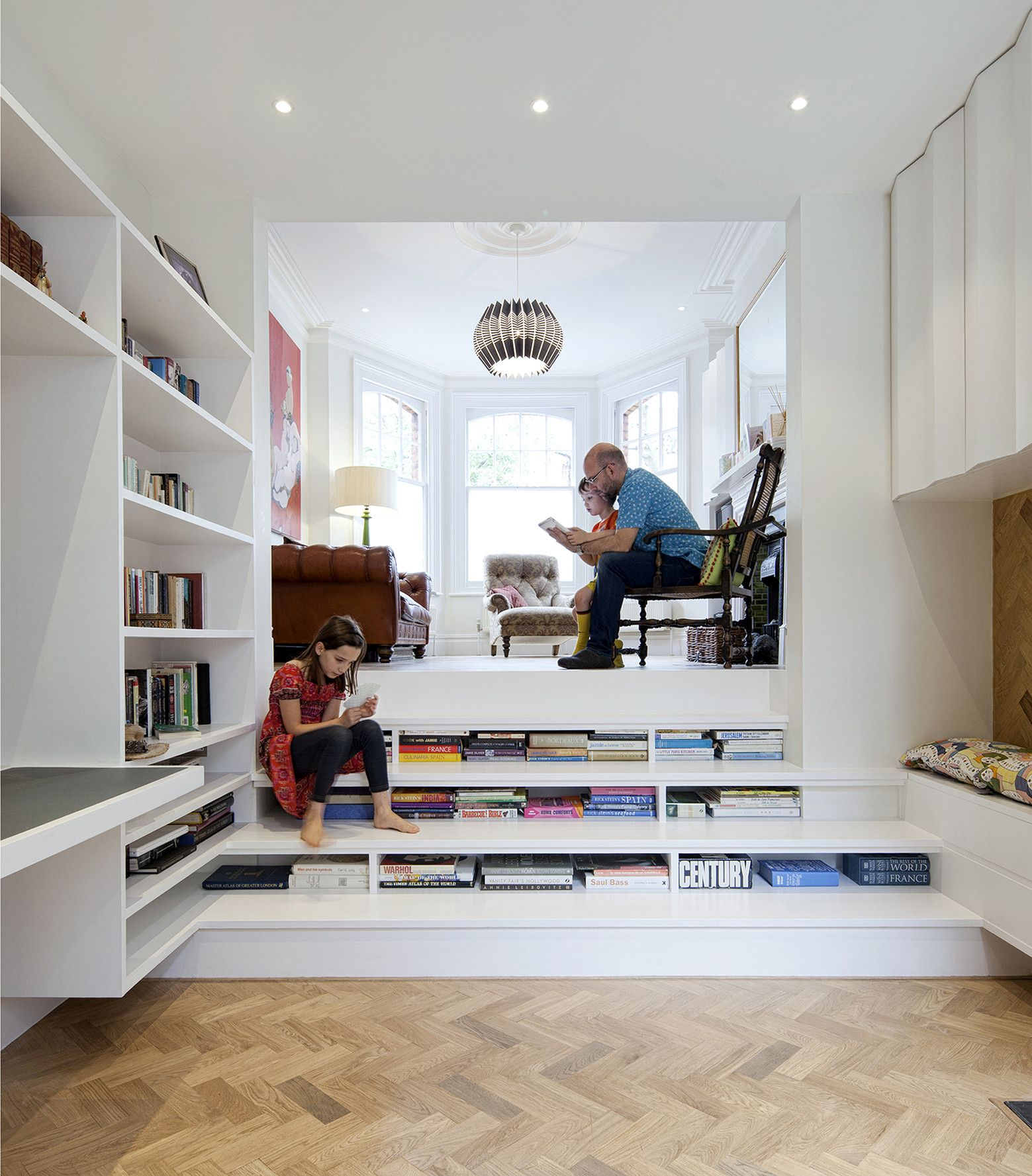 bookshelves built into the staircase is a very cool and space saving idea for a modern home