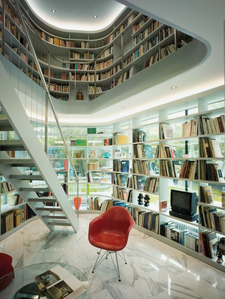 a modern sculptural library all covered with built in bookshelves and a sculptural second floor plus a chair and much natural light