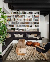 a modern black and white library with white bookshelves, an L-shaped black sofa, a wooden slab table and a black chair