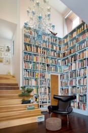 a modern library nook with very tall blue bookshelves, a blue chandelier and a black leather chair