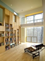 a modern and sleek library done in neutrals, with lots of bookshelves, a double-height window and a comfy lounger