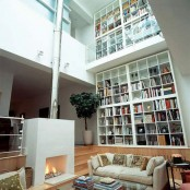 a double-height white library with lots of bookshelves, a sleek white fireplace and some neutral sitting furnitureplus skylights over it