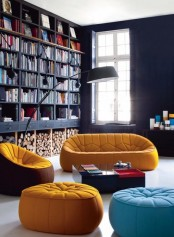 a modern black library with built-in bookshelves and laconic and colorful modern sitting furniture plus a floor lamp