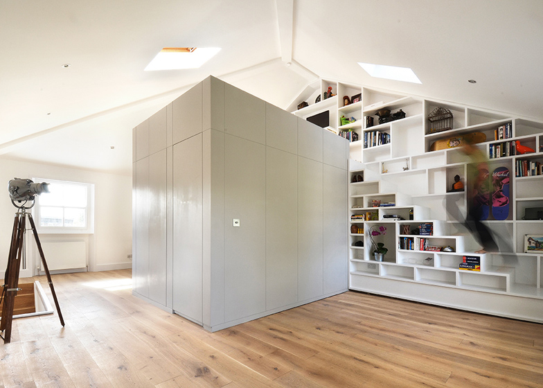 a modern home library with built in bookshelves placed on the wall and reaching the ceiling