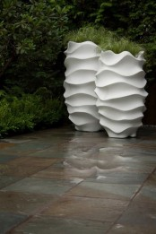 a modern tall white surrealistic planters with greenery will give a modern and atful feel to your backyard