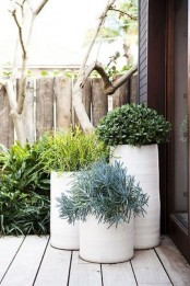 tall white planters with a slight texture and green plants will give your backyard a modern and fresh feel
