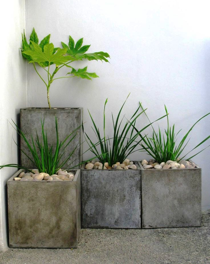 a concrete square planter arrangement with greenery and pebbles is a cool minimalist decoration for a backyard