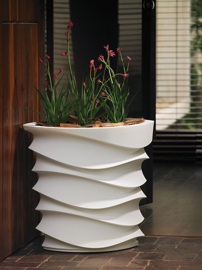 a white patterned tall planter will accent your blooms or greenery and will add a modern feel to the space
