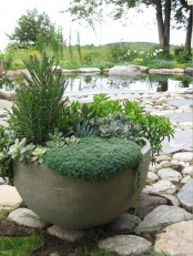 an oversized concrete bowl planter with succulents and greenery is a cool piece for a modern space