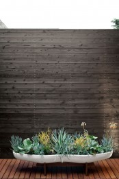 a long curved low white planter with succulents and greenery is a very cool piece for any modern space