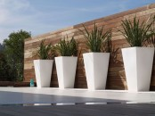 tall white planters placed in a row will highlight your outdoor space giving it a modern feel and a chic look