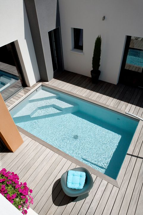 modern wooden deck with a small outdoor pool