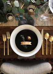 a modern Thanksgiving tablescape with a woven table runner, greenery, gold glitter, gold cutlery and black and white plates