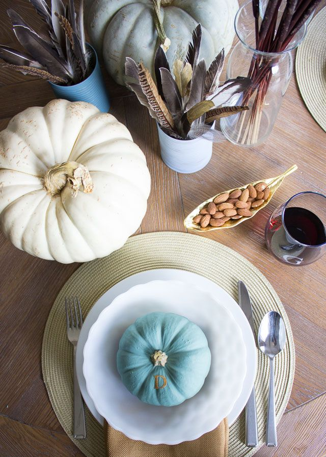 a modern farmhouse Thanksgiving tablescape with pale and pastel pumpkins, feathers and pastel porcelain is very chic
