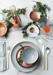 a modern Thanksgiving tablescape with speckled porcelain, greenery, candles and cutlery is a chic idea