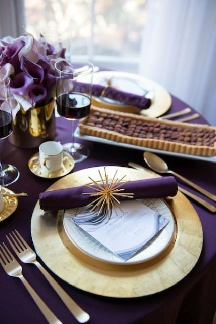 a bold modern Thanksgiving tablescape with a purple tablecloth and napkins, gold chargers, cutlery and saucepans and deep purple blooms
