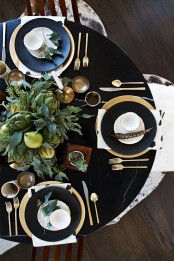 a stylish modern Thanksgiving tablescape in black, with a lush greenery, pears and artichoke centerpiece, black chargers and gold cutlery