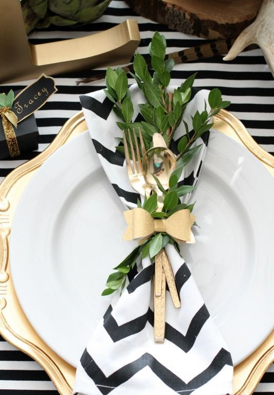 a modern Thanksgiving tablescape with a striped tablecloth and a chevron napkin, a gold chargers and gold cutlery, greenery attached to the napkin