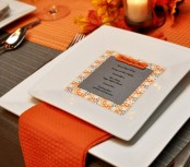 a modern colorful Thanksgiving tablescape in grey and orange, with square plates, a grey card and a bright orange runner and napkins