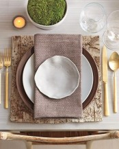 a modern farmhouse Thanksgiving tablescape with a bark placemat, gold cutlery, candles and moss in a planter