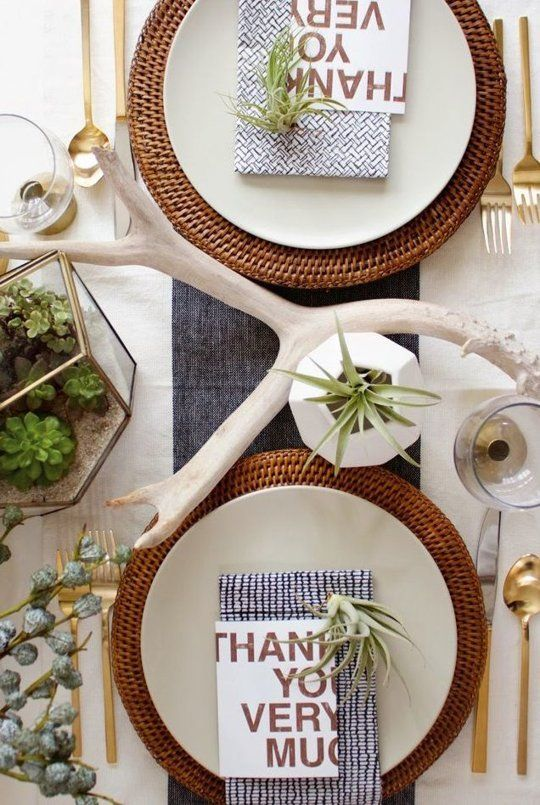 a modern Thanksgiving tablescape with succulents in a terrarium, greenery, antlers, woven chargers and gold cutlery is super chic