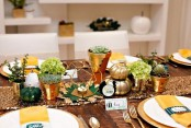 a modern colorful Thanksgiving tablescape with a glitter runner, gold, green and white pumpkins, potted greenery and colorful napkins