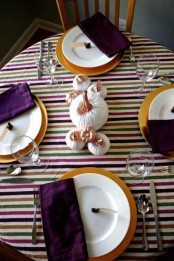 a modenr colorful Thanksgiving tablescape with a striped tablecloth, pumpkins, gilded chargers, deep purple napkins is a very chic one