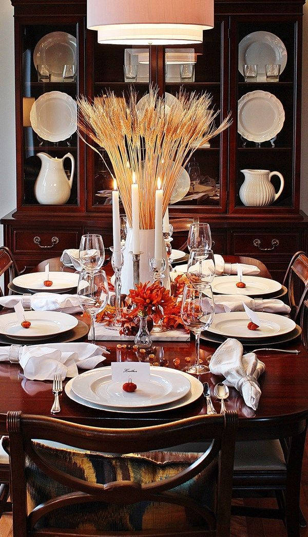 a rustic Thanksgiving tablescape with white porcelain, mini pumpkins, candles, bright blooms and wheat in a vase is a pretty one