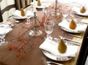 a simple and modern Thanksgiving tablescape with a brown table runner, berries on branches, pears and candles plus patterned porcelain