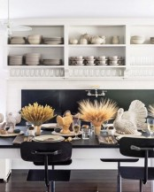 a stylish modern Thanksgiving tablescape with taupe napkins and table runners, wheat in vases, turkeys, candles and gold cutlery