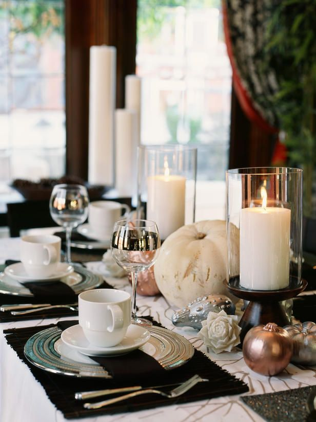 an elegant and contrasting Thanksgiving tablescape with brown placemats and a table runner, gilded pumpkins and candles in glasses is chic