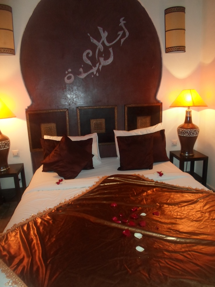 a Moroccan bedroom done in rust, brown and neutrals, with ornate lamps and a statement artwork on the wall
