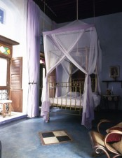 a Moroccan bedroom with a gold bed and lavender canopy, shutters and a mosaic balcony entrance, carved wooden furniture