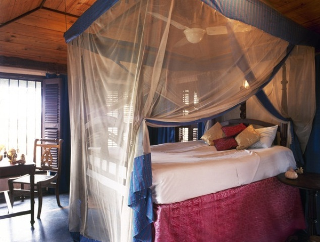 a bedroom with dark stained wood, a carved wooden bed and sheer and colored cnaopy in layers over the bed