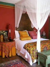 a bright Eastern bedroom in red, pink, ocher, with a dark stained wooden bed and bright textiles