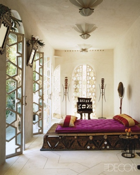 a neutral Moroccan bedroom with a star printed floor, ornate mirrors and lamps and a unique carved platform bed