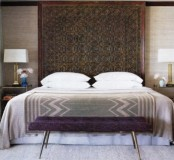 a Moroccan feel is given with a rug on the wall, printed bedding and a purple bench at the foot of the bed