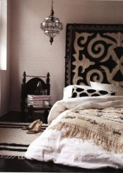 a monochromatic Moroccan living room with a patterned rug, a lantern, a carved chair and a Moroccan wedding blanket