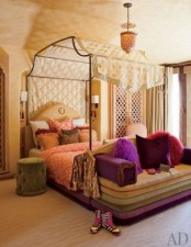 a bright Moroccan bedroom with a whimsy bed with a unique canopy and super bright bedding and a velvet upholstered bench