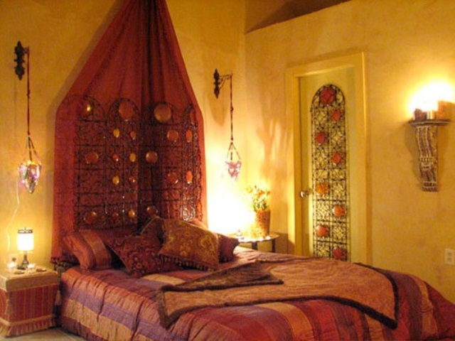 a warm colored Moroccan bedroom with hanging lanterns, a mosaic door and colorful textiles