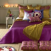 a neutral Moroccan bedroom done with jute, carved tables and lamps and super bright fuchsia and mustard bedding