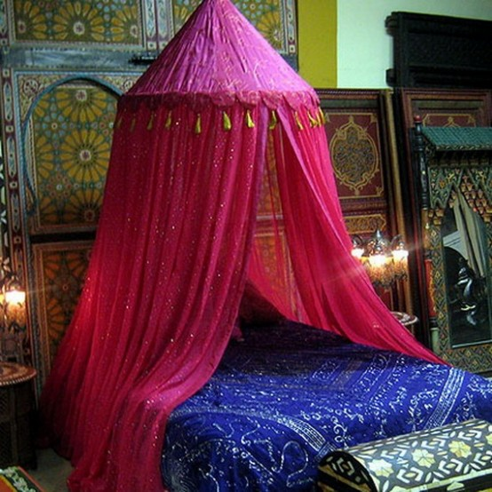 a bright Moroccan bedroom in blue and pink, with lots of patterns and an ornate mirror