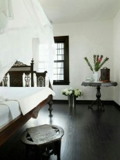 a monochromatic bedroom with a carved wodoen bed, chair and table and neutral bedding and a canopy