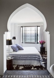 a contrasting Moroccan bedroom in an alcove, an ornate window, a carved wooden table and a faux animal skin