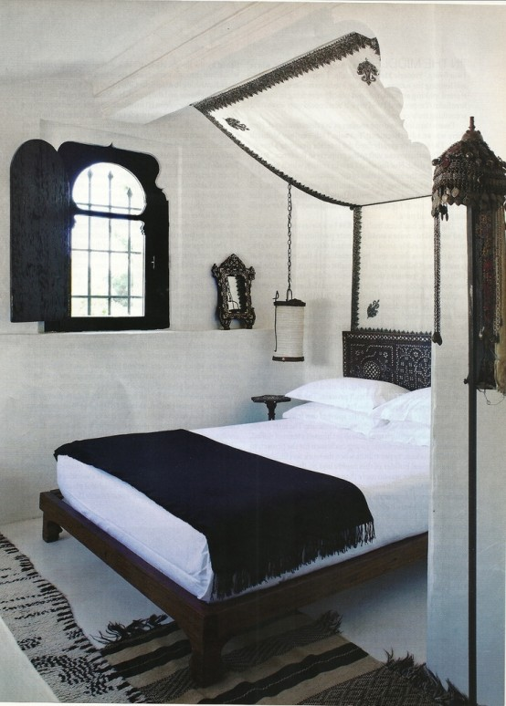 a black and white Moroccan bedroom with a shuttered window, a dark stained bed, a canopy and hanging lanterns
