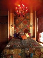 super colorful and printed textiles, a red chandelier and pillows create a unique and bright sleeping space