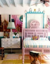 a carved pink bed and a rattan stool give a slight Moroccan feel to the bedroom